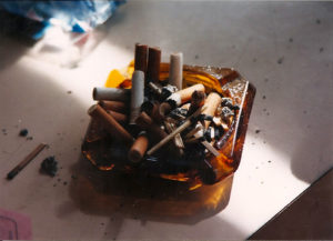 image of a golden semi-translucent ash tray on top of a white wooden table, covered in old cigarette butts. a slit of light in a rectangular slat falls from the top left corner of the image to the bottom right.