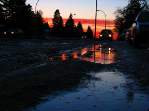 image of a road covered in melting snow, with a giant puddle reflecting the sky. one of the puddles, closest to the camera, is dark blue, the other puddle, further away, is red and orange and glistening with a lone car's headlights. the car, road, and trees are black from the dawn. the top of the sky is a pale blue and pink shell color, the bottom thick bands of red and gold for the sunrise.
