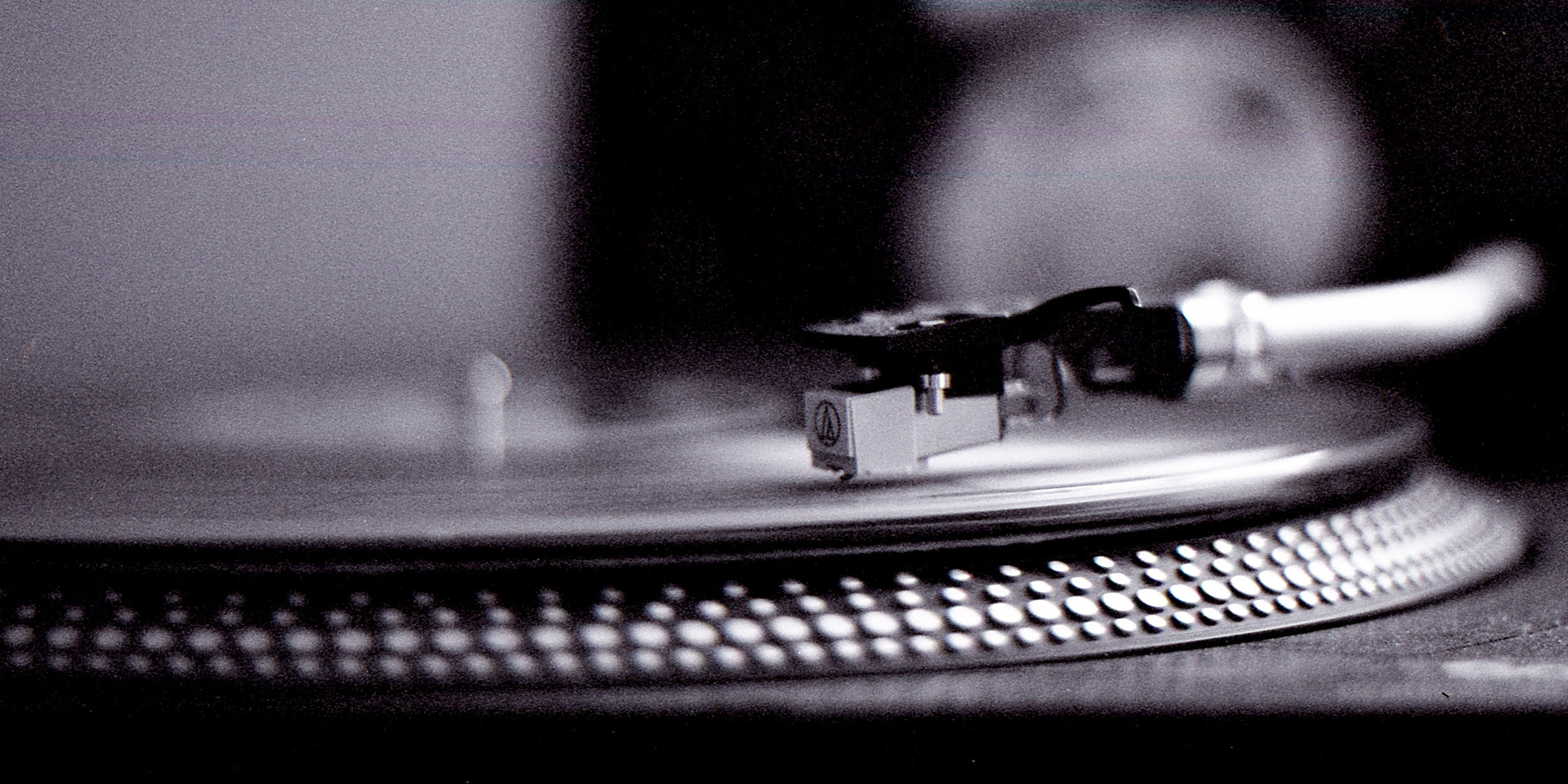 close up side view of a record player, grainy image, black and white.