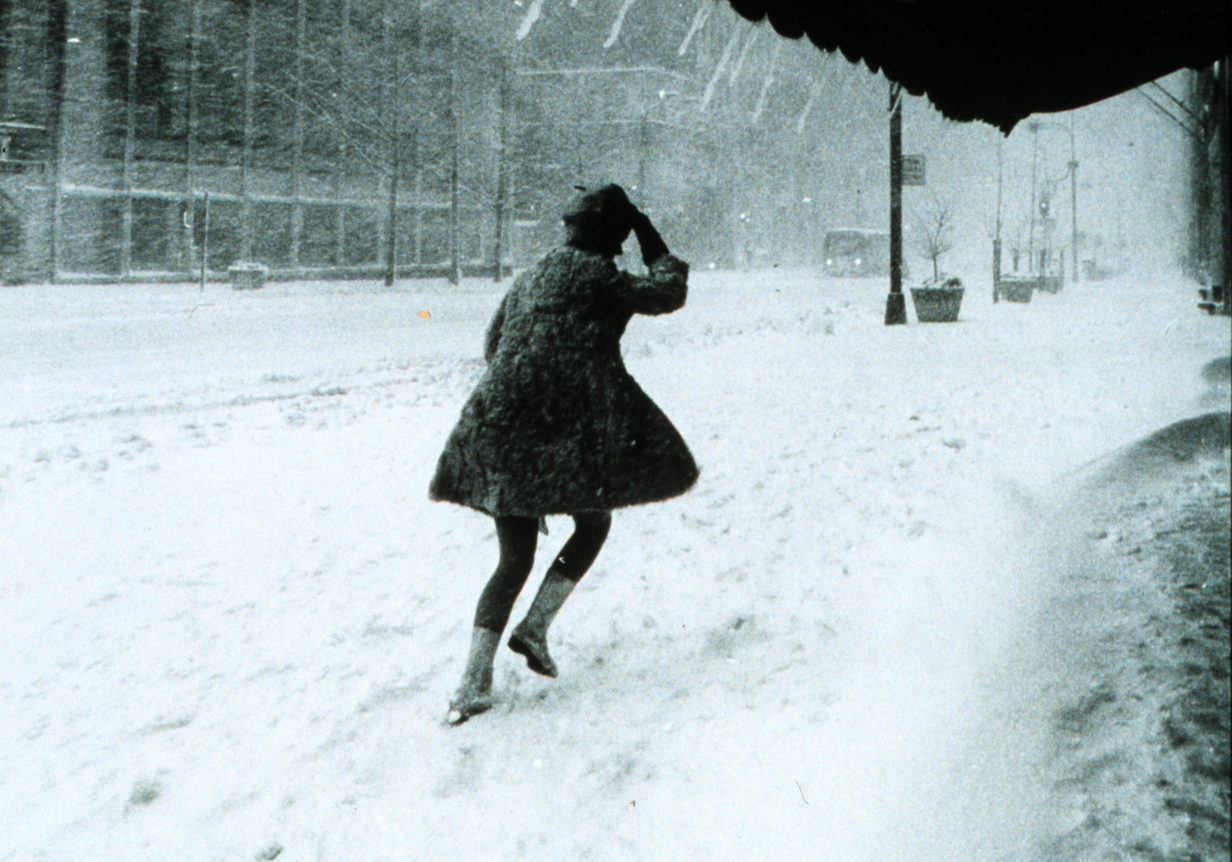 image of a woman in a green dress running away from the viewer in a snowstorm. she is partially under a dark awning, behind her, her footprints make tracks in the new snow.