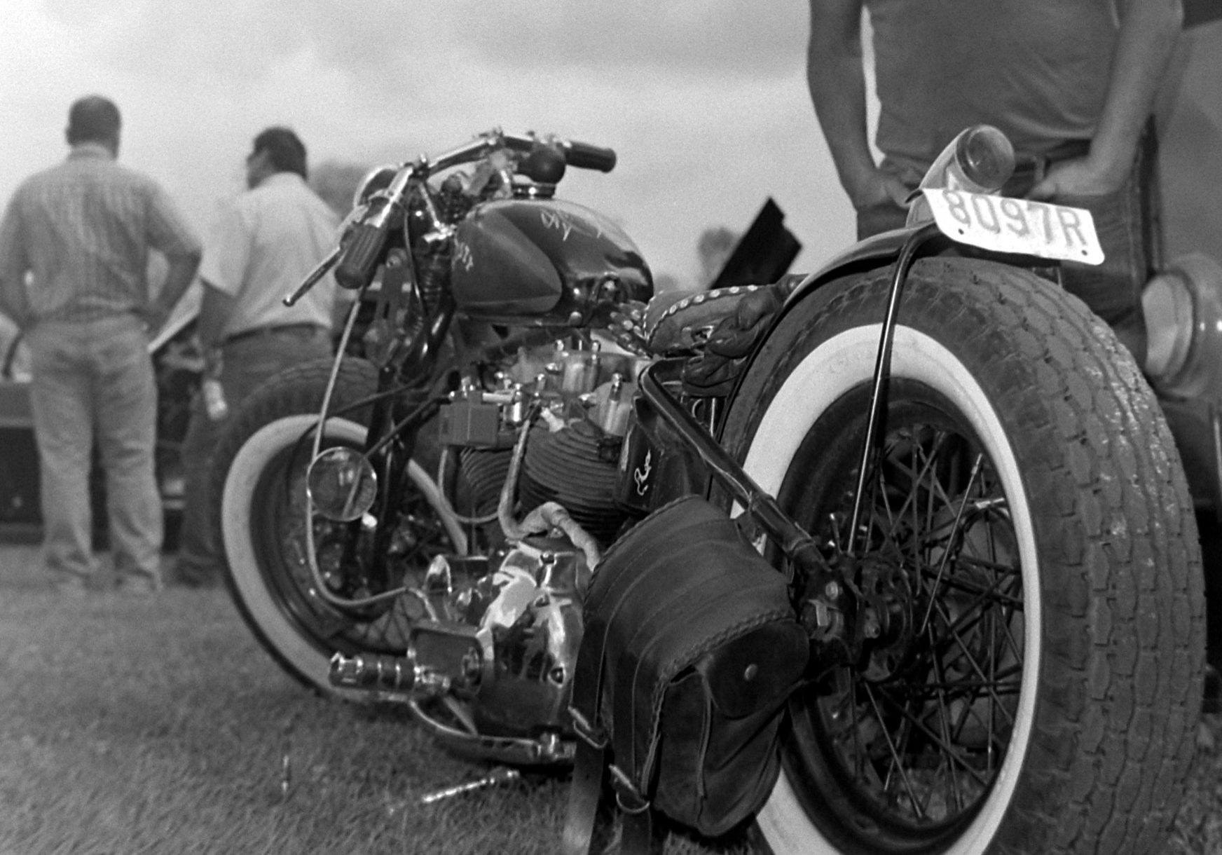 close up image of an old motorcycle propped up in grass, with a man with his hands in his pockets standing behind it, and two men far off in the left hand corner of the frame looking away.