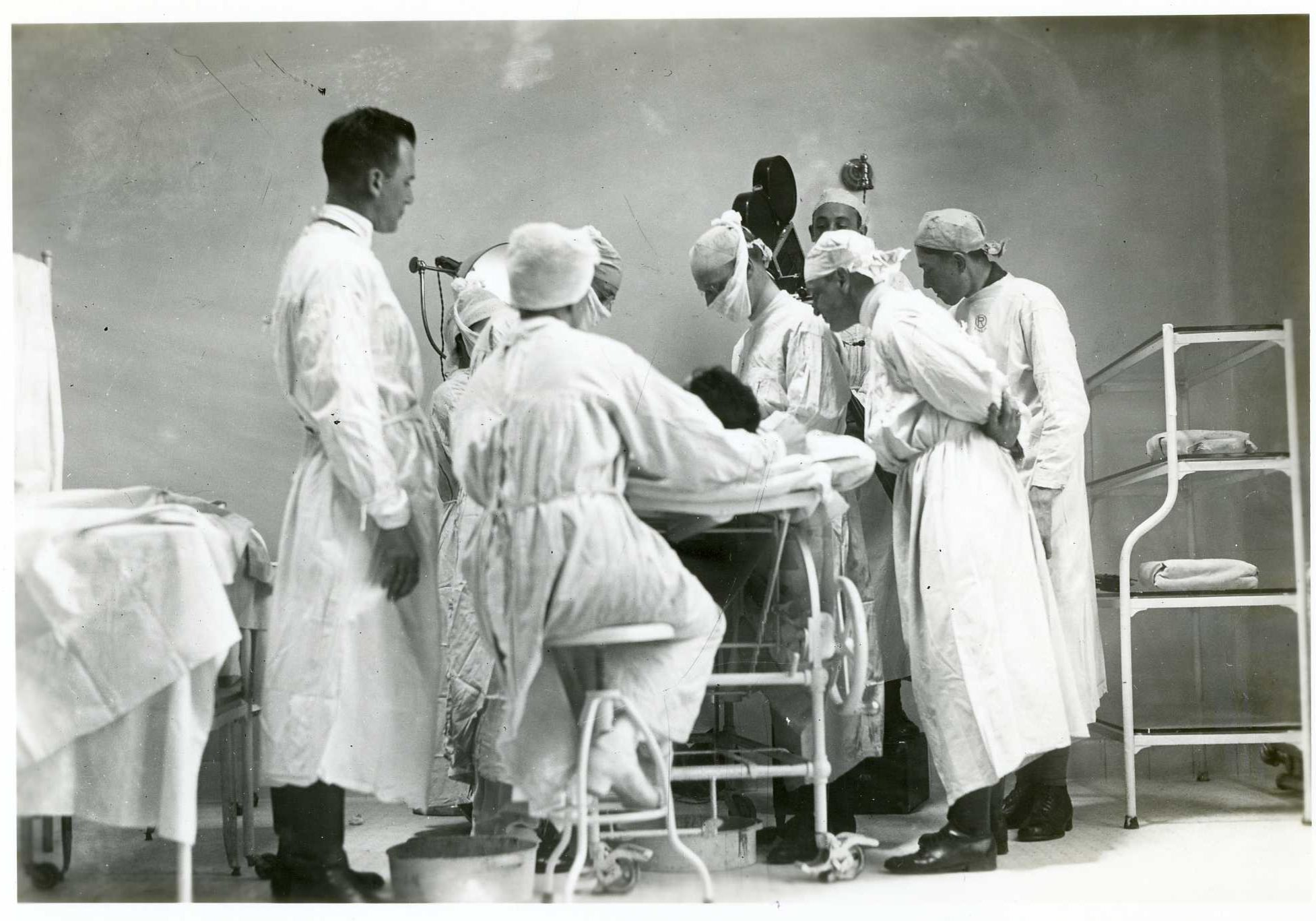 old image of doctors and nurses gathered around operating table.