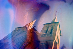 upward shot of the top of a large cathedral with two towers flanking the center structure, both with a turret at the very top (a steeple). the image is overlaid with light leaks of purple and red, and while the cathedral is lit by the sun, the shadows are green. it looks like the film was ruined, overexposed, or opened up, so the image is saturated with watercolor-ish colors.