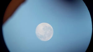 image of white moon in pale blue sky, seen through a round circle rimming the edges of the frame.