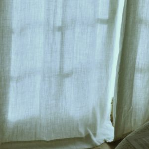 image of soft, pale bluish-gray curtains with a late-afternoon light casting soft shadows of the window bars into the fabric, hang down most of the image, bunching a tiny bit at the bottom sliver to reveal a wooden surface. they are closed and fall like drapes.