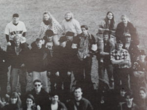 Old image of a group of highschool kids standing around, some of the girls on boy's shoulders.