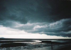 shot of a the edge of the seashore, the water is dark and shiny, and low hanging dark and blue foreboding clouds low on the horizon.