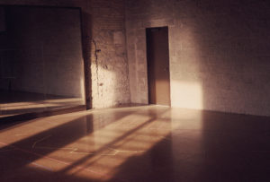 basement rehearsal space, empty room with brick walls and concrete floors, with sunlight lighting the walls.