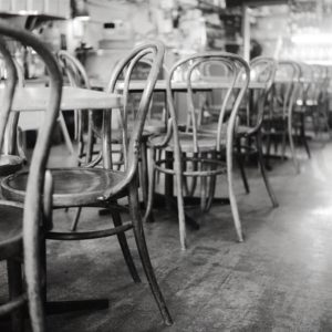 close up image of old wooden chairs lined against tables