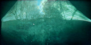 green murky image that look slightly metallic and/or as if it were shot through a green windowshield, looks at a hill crested with thick trees