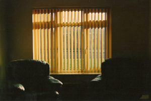 Image of two dark green chairs in shadows on opposite sides of a window that is casting golden light throw yellow shutters.