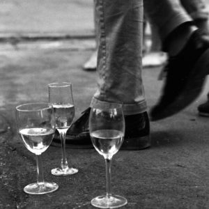 three champagne glasses set on the ground in front of feet walking away from the champagne. the image is in black and white and made with film, it is grainy and has a nostalgic feel to it.