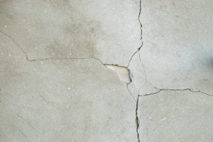 image of a large crack in pale and soft looking warmish concrete