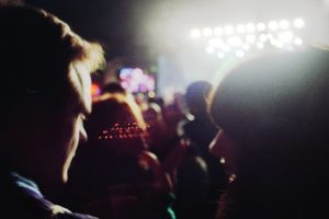 blurry image of rim light around faces at a concert, two people turned toward each other. way in front of them, you can see a stage with lights and blurred heads of people, dark except for the warm light in the darkness on their edges.