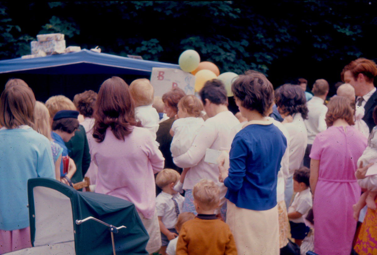 a gathering of people, mostly women, holding children and by balloons, in pastel colors. they are all facing away. there is a large crowd.