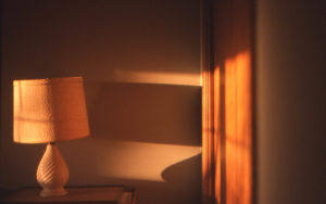 early morning light against a wall and a lamp with a wide shade. the room is yellow and gold and warm.