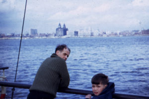image of a small boy and his father on a ferry, it looks cold.