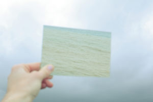 a blurry hand holding a blurry photo of the sea against a pale sea gray with hints of blue sky