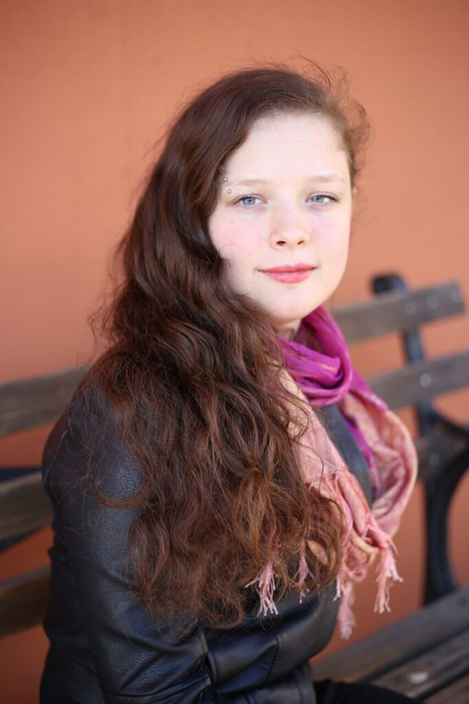 Headshot of Molly McCully Brown staring into the camera with a gentle smile on her face. She is sitting on a dark wooden bench in front of a pinkish orange wall. Her long chestnut hair is over her shoulder and she is wearing a leather jacket and a pink and peach scarf.