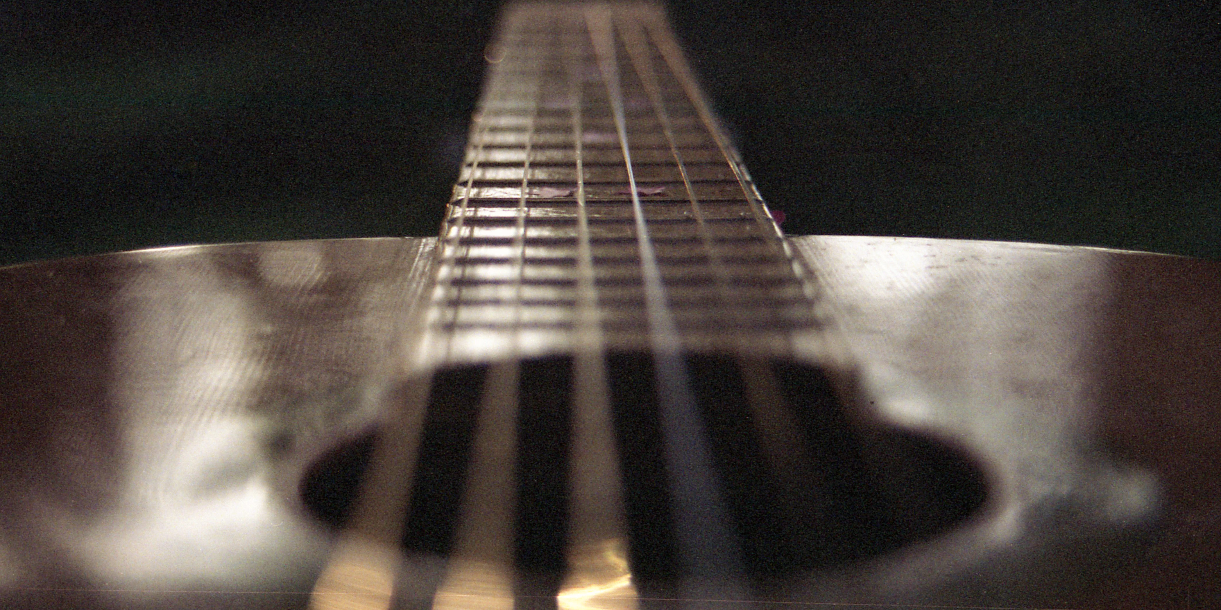 image of the top of a guitar nearly at the same eye level as the viewer, with the strings moving from the body of the guitar to off the center in a blurry line.